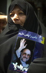 An Iranian woman in black chador holds a photo of President Mohammad Khatami as he arrives to a mosq..