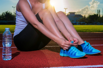 Woman tying shoelaces on running racetrack, red rubber racetracks in outdoor stadium. Closeup of female sport fitness runner getting ready for jogging.