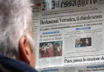 A man reads a newspaper featuring a story about former prime minister Silvio Berlusconi and his wife Veronica in Rome