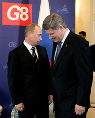 Russia's President Putin and Canada's PM Harper take their seats at the start of a bilateral meeting in St. Petersburg