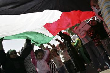 Jordanian children hold a Jordanian national flag during a rally in Amman
