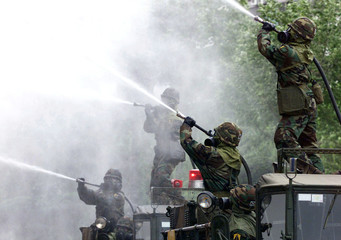KOREAN SOLDIERS SPRAY WATER ON A MOCK FIRE DURING AN ANTI-TERROR DRILLIN SEOUL.
