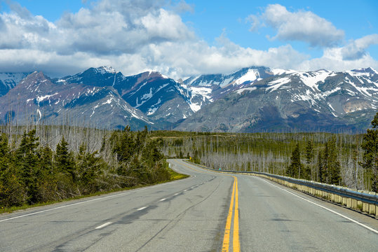 Highway to the Glaciers - A cloudy spring morning view of U.S. Route 89 extending towards snow-capped high mountain peaks in Glacier National Park, Montana, USA.