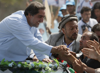 Afghan presidential candidate Abdullah Abdullah is mobbed by supporters as he arrives to give a campaign speech at the Shrine of Hazrat Ali in Mazar-i-Sharif in Balkh province