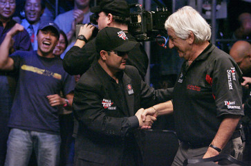 Yang of California shakes hands with Rahme of South Africa after knocking Rahme out from the final table during the World Series of Poker main event at the Rio Hotel and Casino in Las Vegas