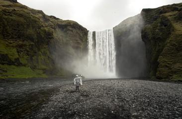 Tourist takes photos of Skogafoss waterfall near Skogar on Iceland's southern coast