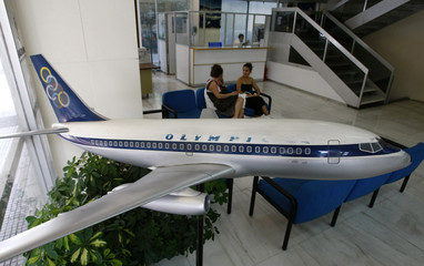 Passengers sit inside an Olympic Airlines ticket office in Athens