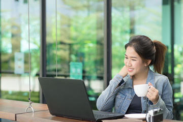 Beautiful young Asian girl working at a coffee shop with a laptop.female freelancer connecting to internet via computer. Woman is feeling happy and enjoy moment in the morning.