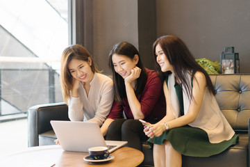 Three beautiful Asian girls using smartphone and laptop, chatting on sofa at cafe, modern lifestyle with gadget technology or working woman on casual business meeting outside office concept.