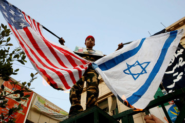 Protester holds burning Israeli and US flags during protest in Cairo