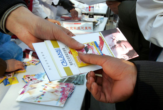 A Chinese volunteer hands free condom and AIDS prevention brochures in Beijing.