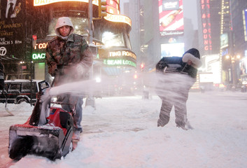 Maintenance workers clear a walkway as heavy snow falls in New York's Times Square