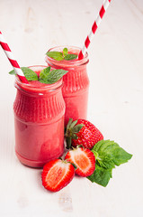 Freshly blended red strawberry fruit smoothie in glass jars with straw, mint leaf, cut ripe berry. White wooden board background, copy space.