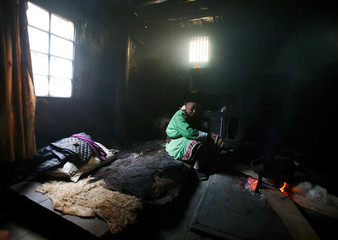 Tibetan man sits in his house  in Baima township