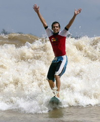 BRAZILIAN SURFER CARNEIRO CELEBRATES AS CATCHES A WAVE ON THE MEARIMRIVER IN THE AMAZONIAN JUNGLE.