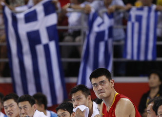Greek flags hang in the background as China's Yao Ming watches his team mates during their men's Group A basketball game against Greece at the Beijing 2008 Olympic Games