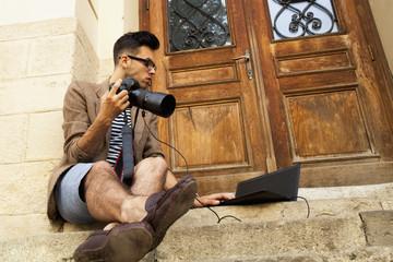 Young photographer looking at photographs on laptop. Photographer selecting photos.