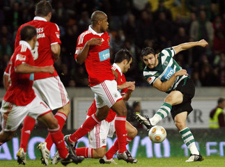 Sporting's Vukcevic  kicks the ball next to Benfica players during their Portuguese Premier League soccer match in Lisbon