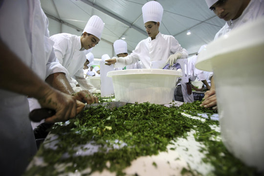 Lebanese chefs chop parsley as they prepare to make Tabbouleh, a traditional Lebanese salad, in Beirut