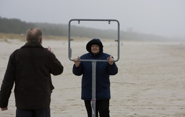 A woman poses behind a removed sign at a former no-go zone that cut across one of Europe's most beautiful beaches into the Baltic Sea at German-Polish border checkpoint Ahlbeck-Swinemuende