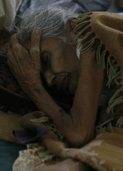 A woman lies on a bed in a ward of the local hospital in the town of Jeypore
