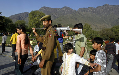 A policeman patrols as people throng a Mughal garden during Baisakhi festival in Nishat