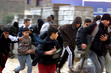 PALESTINIANS RUN FOR COVER AFTER ISRAELI TANKS FIRE ON THEM IN BEITHANOUN.