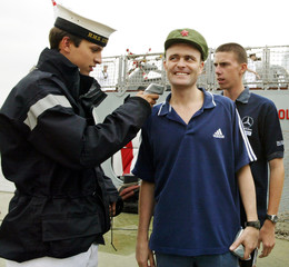 CREW CHECKS THE TEMPERATURE OF SAILOR WEARING A MAO CAP IN SHANGHAI.
