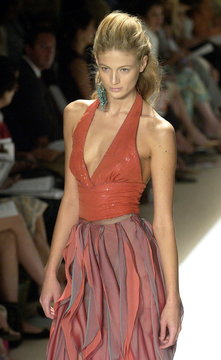 A model wears a desert rose sequined halter and iridescent chiffon jabot skirt during contemporary f..