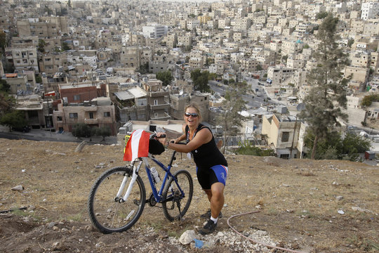 Peham-Struss from Austria, member of Follow the Women Foundation, smiles as she holds her bicycle during a tour at Amman citadel
