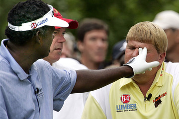 Fiji's Singh sticks his finger in the eye of Daly to clear a bug that flew into his left eye during ...