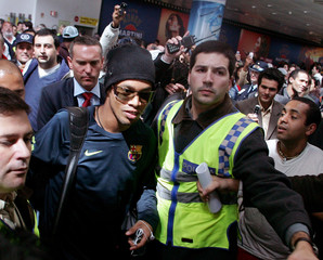 FC Barcelona's Ronaldinho surrounded by supporters on arrival at Lisbon airport