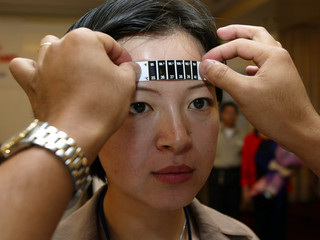 A HEALTH WORKER TAKES THE TEMPERATURE OF A CHINESE DELEGATE DURING ASARS FORUM IN PAMPANGA ...