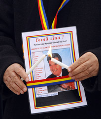 A man lights candles next to a picture of Romania's late communist dictator Nicolae Ceausescu in Bucharest
