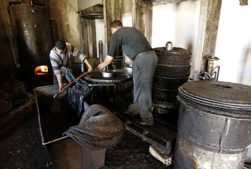 Workers prepare to press olive paste to extract oil at a traditional oil works in the eastern village of Tazmelt