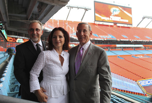 Music producer Emilio Estefan and his wife singer Gloria and Dolphins team owner Ross pose for pictures in Miami