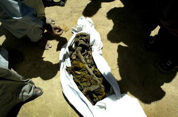 AN IRAQI MAN PLACES AN IDENTITY CARD ON TOP OF REMAINS AT A SUSPECTED MASS GRAVE THAT WAS UNCOVERED NORTH OF NAJAF