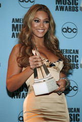 Beyonce poses backstage in photo room with her International Artist Award of Excellence in Los Angeles