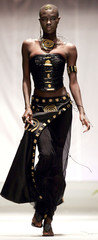A model displays a dress with traditional African brass adornment and modern bead work created by Ma..