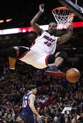 Miami Heat 's Haslem dunks to score as Atlanta Hawks' Bibby looks on in background during Game 3 of their NBA Eastern Conference playoff basketball series in Miami