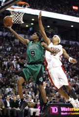 Boston Celtics guard Rajon Rondo scores past Toronto Raptors defender Jamario Moon during their NBA basketball game in Toronto