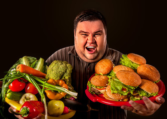 Diet fat man who makes choice between healthy and unhealthy food . Overweight male with hamburgers and vegetables trays trying to lose weight first time Hamburgers and vegetables are held by a fat man