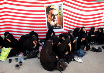 Women sit under picture of Iran's Late Leader Ayatollah Khomeini during religious ceremony in Tehran