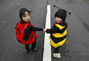 Girls in ladybug and bee outfits take part in Halloween parade in Tokyo