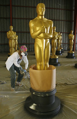 Scenic artist Gayle Etcheverry sprays a fresh coat of paint on a large Oscar statue near Los Angeles