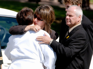 Corporal Keller's parents hug Padre Kean-Newbook after funeral near Edmonton
