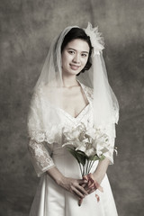 Portrait of a young beautiful bride holding flower