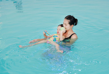 Mother and child swimming in the pool. Happy young woman teaching her daughter to swim.
