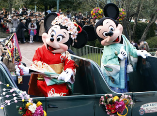 Disney cartoon characters Mickey (R) and Minnie Mouse, dressed in kimonos, wave from an open car during a New Years parade at Tokyo Disneyland in Urayasu