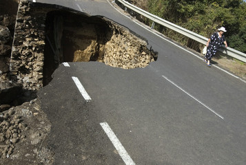 A woman walks on the damaged TF326 road after a portion of it collapsed after storms, near the Palo Blanco village on Spain's Canary island of Tenerife